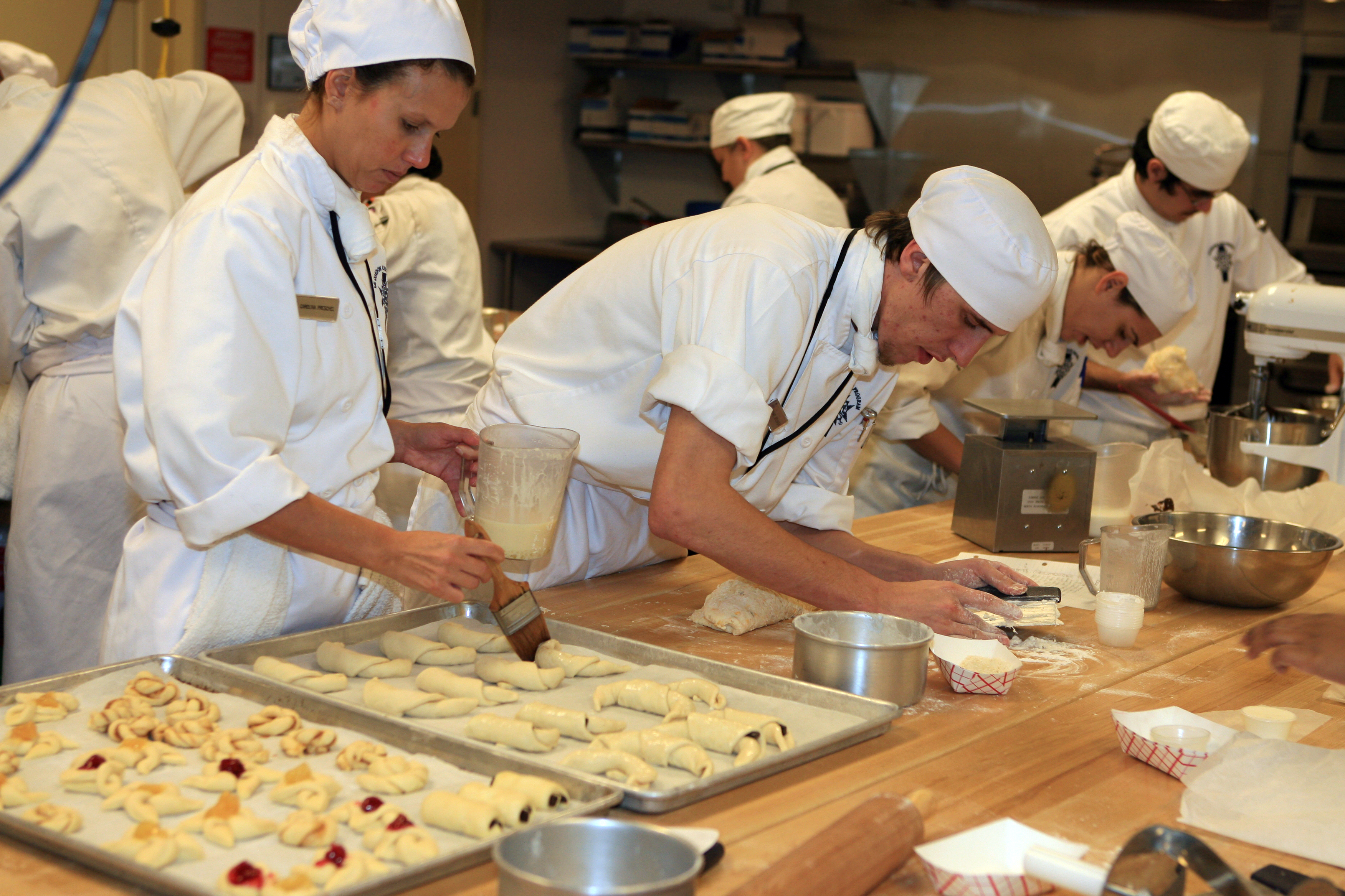 Bakers in white uniforms and hats put together and garnish homemade pastries